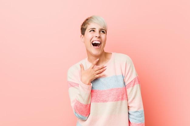 Молодая натуральная женщина громко смеется, держа руку на груди