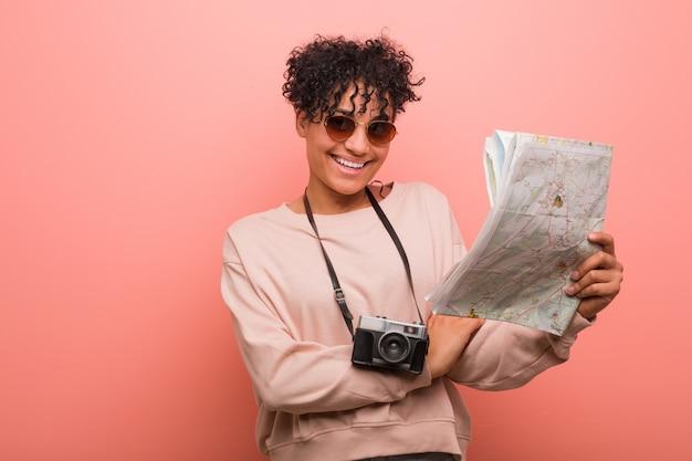 組んだ腕に自信を持って笑顔マップを保持している若い女性