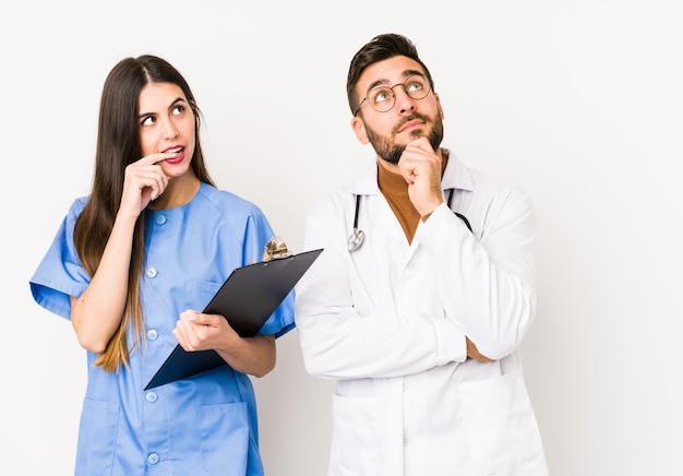 Молодой доктор мужчина и медсестра расслабились, думая о чем-то, глядя на пустое пространство.