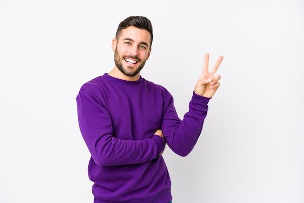 指で平和のシンボルを示すうれしそうなのんきな白い壁に若い白人男。