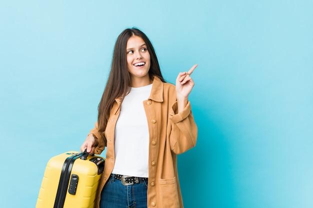 Молодая кавказская женщина держа чемодан усмехаясь жизнерадостно указывая с указательным пальцем прочь.