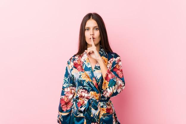 秘密を守る着物パジャマを着ている若い白人女性