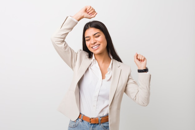 特別な日を祝う白い壁に若いビジネスアラブ女性がジャンプし、エネルギーで腕を上げます。