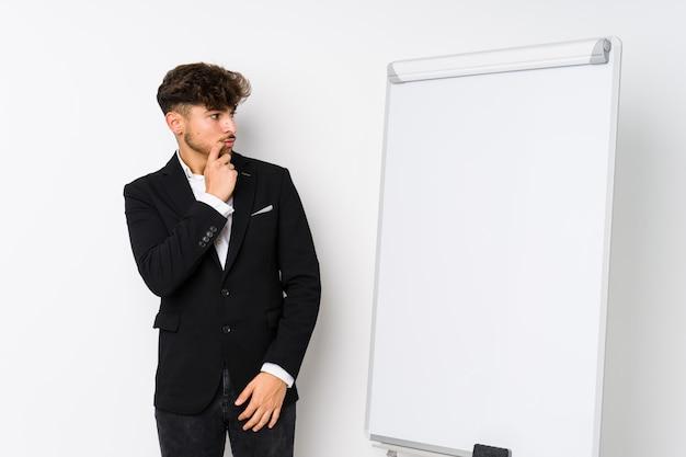 疑わしいと懐疑的な表情で横に探している若いビジネスコーチングアラビア人。