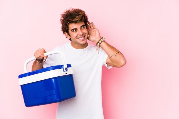 Молодой человек держит портативный холодильник, пытаясь слушать сплетни