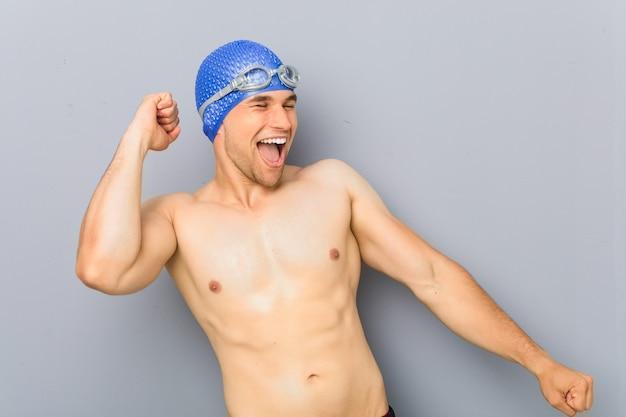 Молодой профессиональный пловец человек танцует и веселится