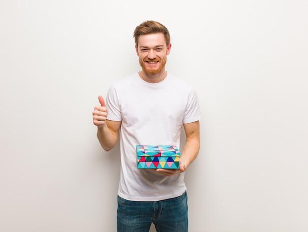 Рыжий молодой человек улыбается и поднимать палец вверх холдинг подарочной коробке.