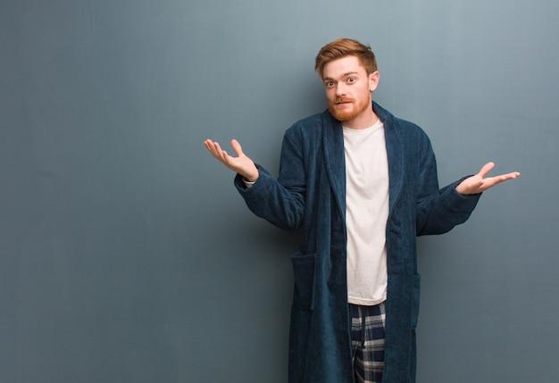 Молодой рыжий мужчина в пижаме смущен и сомнителен
