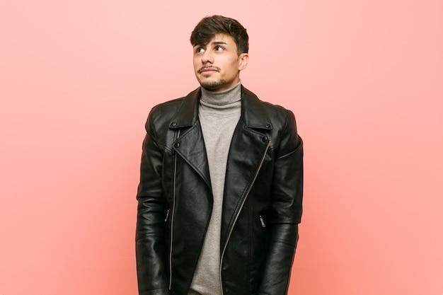 Молодой человек в кожаной куртке мечтает о достижении целей и задач