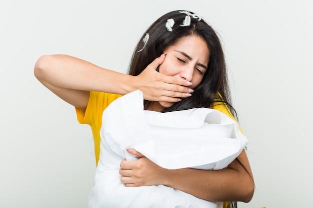 Молодая испанская женщина просыпается и держит подушку