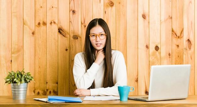 彼女の机で勉強している若い中国人女性がウイルスのため喉の痛みに苦しんでいます。