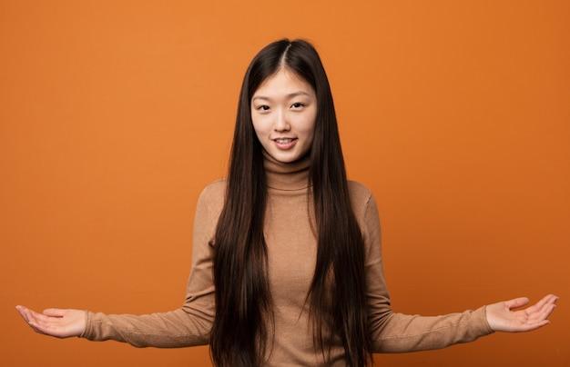 歓迎式を示す若いかなり中国の女性。