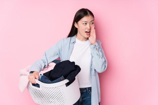 叫び、口の近くに手のひらを保持している汚れた服を拾う若い中国人女性。