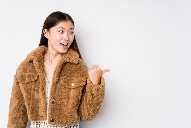 白い壁でポーズをとって若い中国人女性が親指の指で離れて、笑って屈託のないポイントします。