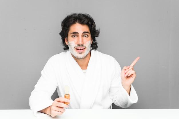 Молодой человек брить бороду, улыбаясь, весело указывая указательным пальцем прочь.