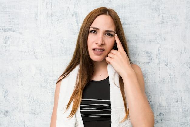 人差し指で失望のジェスチャーを示す若いフィットネス女性