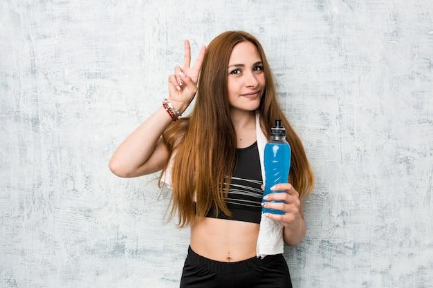 Молодая спортсменка с изотоническим напитком показывает знак победы и широко улыбается