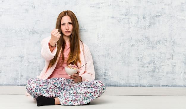 Молодая женщина, держащая миску каши, показывая кулак к камере, агрессивное выражение лица