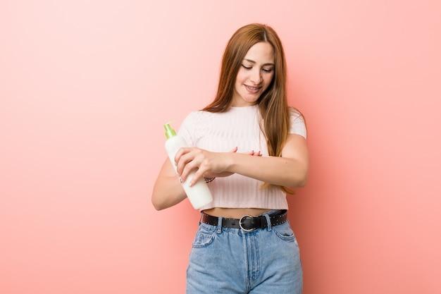 Молодая женщина держит кремовую бутылку
