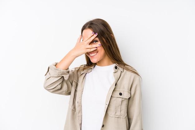 若い女性は、恥ずかしい顔を覆っている指を通してカメラで点滅します