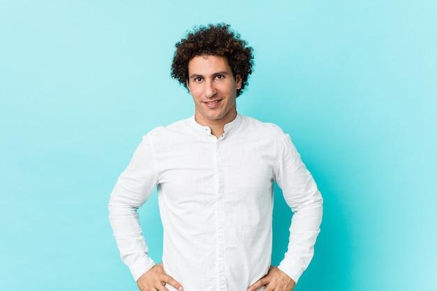 腰に手を自信を持ってエレガントなシャツを着ている若い中年の男性
