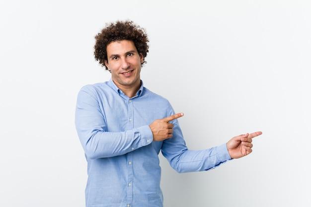 Молодой кудрявый зрелый мужчина в элегантной рубашке возбужденно указывая указательными пальцами