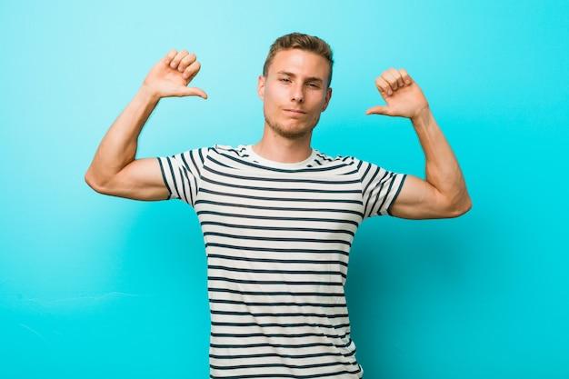 Молодой человек на фоне голубой стены чувствует гордость и уверенность в себе, пример для подражания