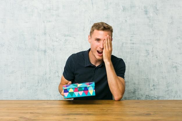 Молодой человек, держащий подарочную коробку на столе, с удовольствием прикрывая половину лица ладонью