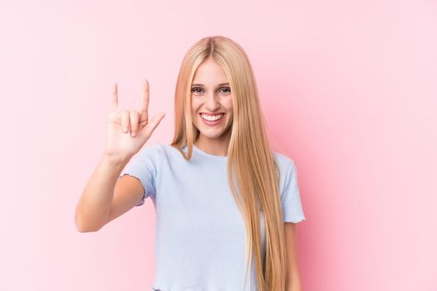 Молодая белокурая женщина на розовой стене показывая жест рожков
