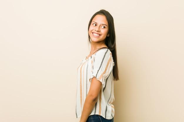Молодая испанская женщина смотрит в сторону, улыбаясь, веселая и приятная.