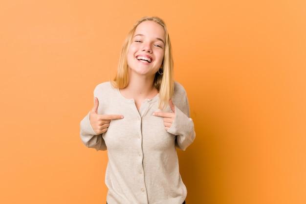 Милый и естественный подросток женщина удивлен, указывая пальцем, широко улыбаясь.