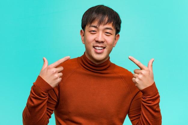 若い中国人男性の笑顔、口を指す