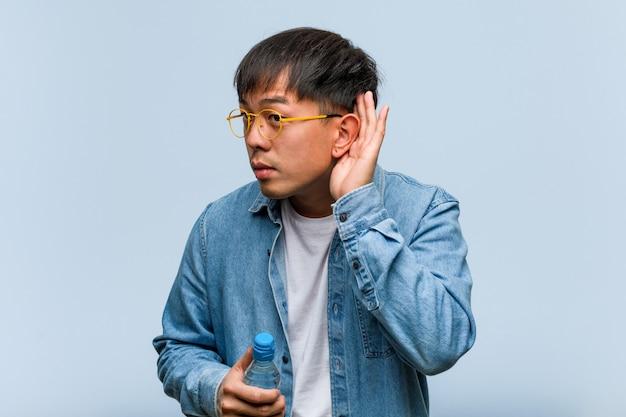 Молодой китайский человек, держащий бутылку с водой, пытается слушать сплетни