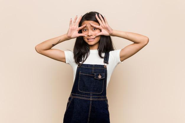 Молодой симпатичный китайский подросток молодая белокурая женщина, носящая пальто против розовой стены, не спускающей глаз, чтобы найти возможность успеха.