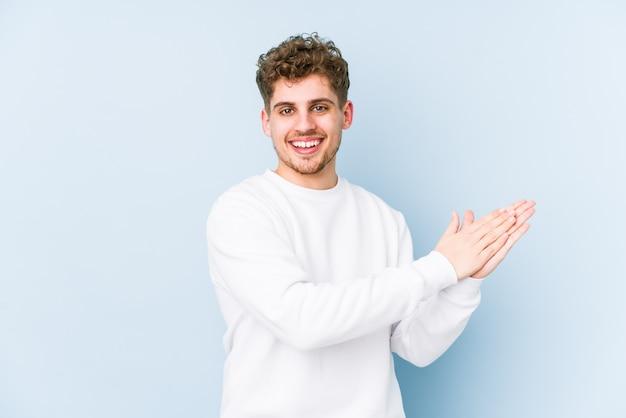 Молодой блондин кудрявый мужчина чувствуя себя энергичным и комфортным, уверенно потирая руки