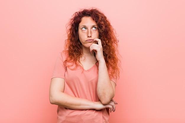 疑わしいと懐疑的な表情で横に探している若い自然で本物の赤毛の女性