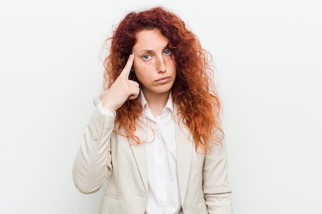 Молодая естественная рыжая бизнес-леди указывая висок с пальцем, думая, сфокусированная на задаче
