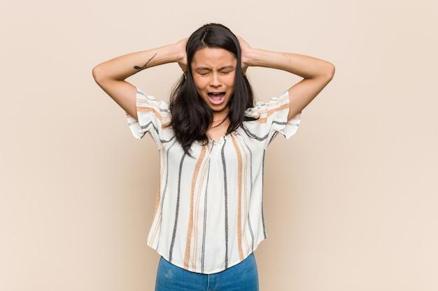 大きなかわいい音を聞かないようにしようと手で耳を覆っている若いかわいい中国のティーンエイジャー。