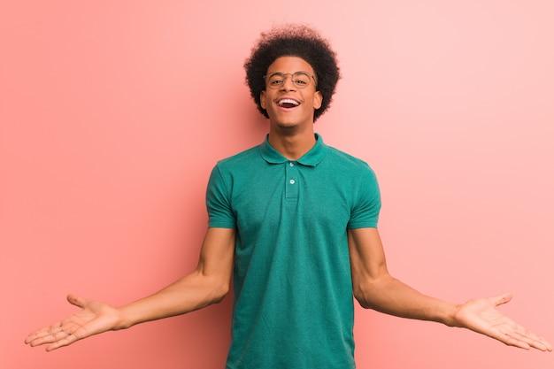 Молодой афроамериканец человек над розовой стеной, приглашая прийти