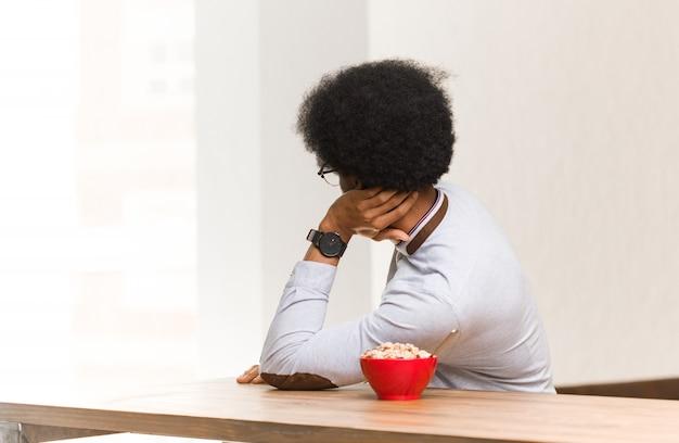 Молодой черный человек завтракает, думая о чем-то