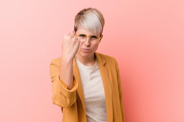 カメラ、積極的な表情に拳を示すカジュアルなビジネス服を着ている若い白人女性。