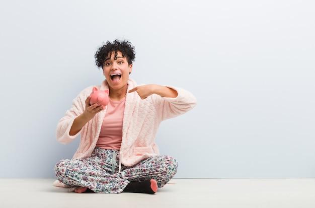 貯金箱に座っている若いアフリカ系アメリカ人女性は、自分自身を指して驚いて、広く笑っています。