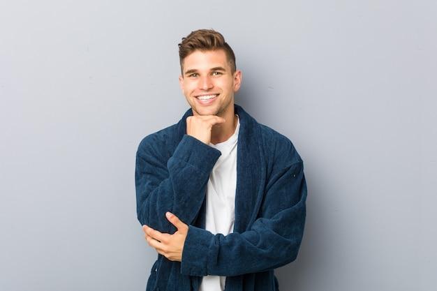 Молодой человек кавказской носить пижаму, улыбаясь счастливым и уверенным, касаясь подбородка рукой.