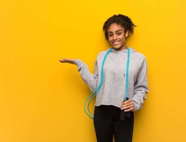 Молодой фитнес черная женщина держит что-то с рукой.