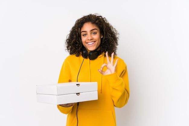 Молодая афро-американская женщина студента держа пиццы жизнерадостные и уверенно показывая одобренный жест.