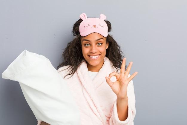 Молодая афро-американская женщина нося пижаму и маску сна держа подушку жизнерадостную и уверенно показывая одобренный жест.