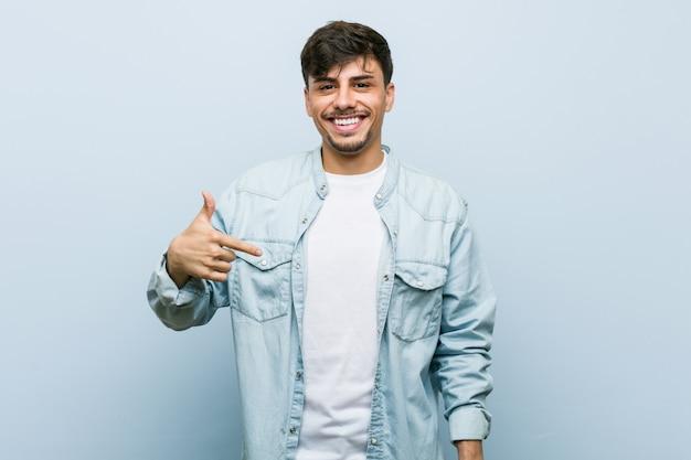 Молодой латиноамериканский крутой мужчина человек, указывая рукой на пустое пространство рубашки, гордый и уверенный