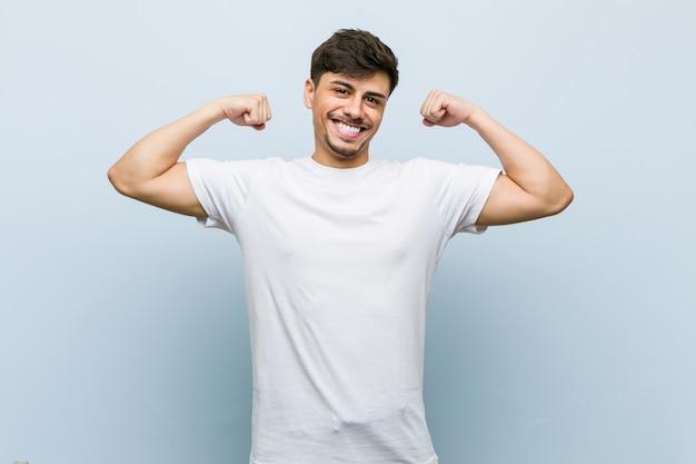 Молодой кавказский человек нося белую футболку показывая жест прочности с оружиями