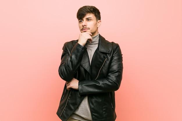 疑い深く懐疑的な表情で横向きの革のジャケットを着ているヒスパニック系の若者。