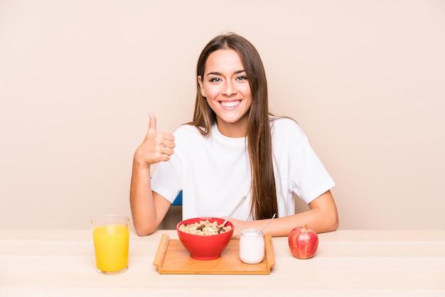 笑みを浮かべて、親指を立てて朝食を持っている若い白人女性
